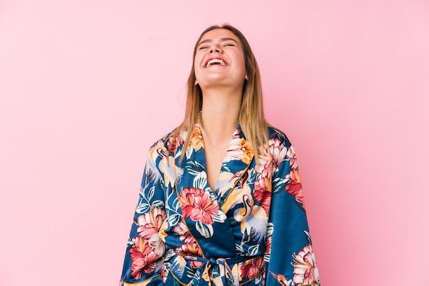 Młoda caucasian kobieta ubrana w piżamę zrelaksowany i szczęśliwy śmiejąc się, szyja wyciągnięta pokazując zęby.