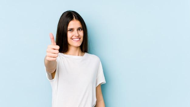 Młoda caucasian kobieta uśmiecha się kciuk up i podnosi na błękit