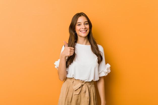 Młoda caucasian kobieta uśmiecha się kciuk up i podnosi