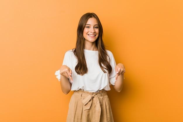Młoda caucasian kobieta wskazuje w dół palcami, pozytywne uczucie.