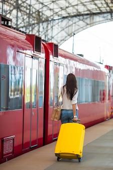 Młoda caucasian kobieta z bagażem przy stacyjnym podróżowaniem pociągiem