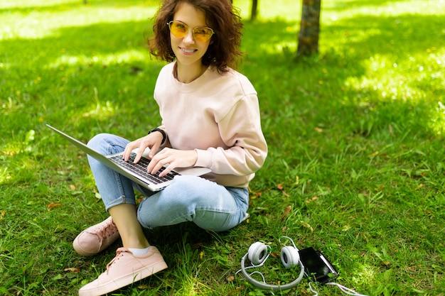 Młoda caucasian kobieta z doskonałym uśmiechem, pulchne usta, okulary chodzi w przyrodzie, siedzi na trawie z laptopem i komunikuje się z przyjaciółmi lub pracuje