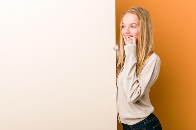 Młoda caucasian kobieta z kopii przestrzenią relaksował główkowanie o coś patrzeje odbitkową przestrzeń.
