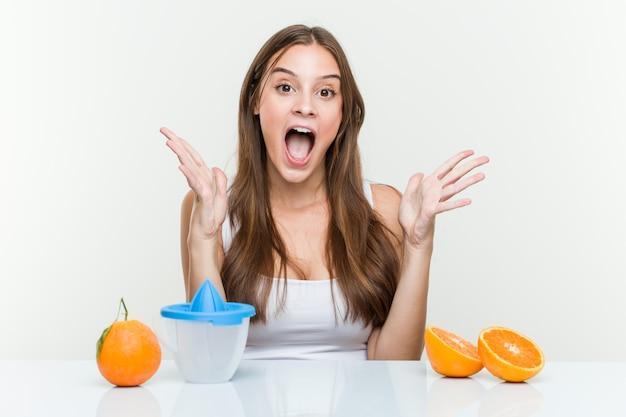 Młoda caucasian kobieta z pomarańczową sokowirówką świętuje zwycięstwo lub sukces
