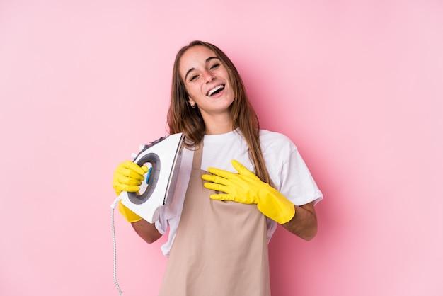 Młoda caucasian kobieta z ubrania żelazem odizolowywającym śmieje się głośno trzymający rękę na klatce piersiowej.