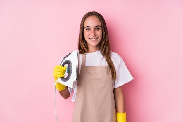Młoda caucasian kobieta z ubrania żelazem odizolowywał szczęśliwego, uśmiechniętego i rozochoconego.