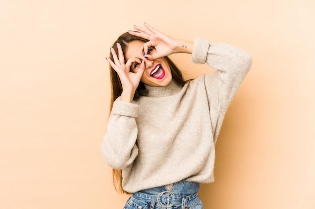Młoda caucasian kobiety en beżu ściana pokazuje ok podpisuje oczy