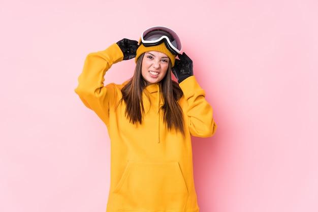Młoda caucasian narciarki kobieta zakrywa ucho z rękami.