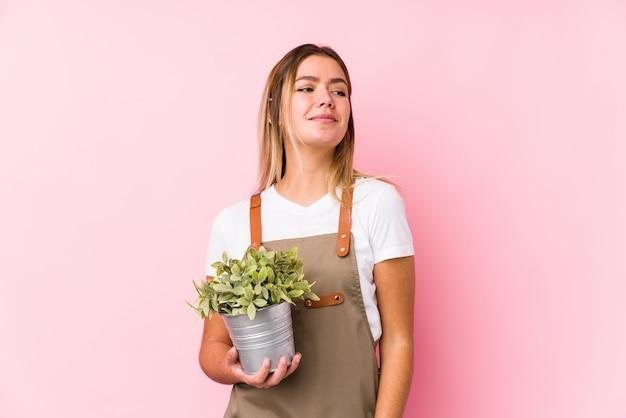 Młoda caucasian ogrodniczka kobieta w różowej ścianie marzy o osiągnięciu celów i zamierzeń