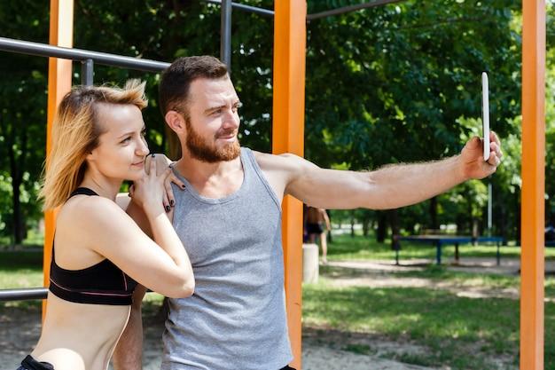 Młoda caucasian para robi selfie fotografii podczas gdy robić sprawności fizycznych ćwiczeniom w parku.