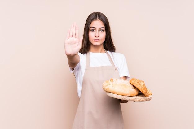 Młoda caucasian piekarz kobieta odizolowywał pozycję z szeroko rozpościerać ręka seansu znaka stopu, zapobiegający ciebie.