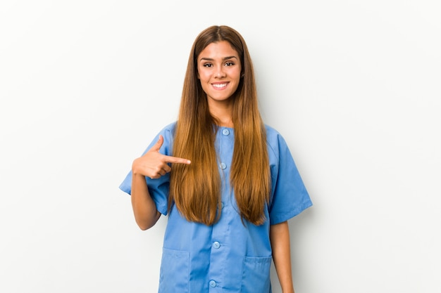 Młoda caucasian pielęgniarki kobiety osoba wskazuje ręką do koszulowej kopii przestrzeni, dumny i ufny