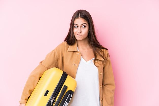 Młoda caucasian podróżnicza kobieta trzyma walizkę isolatedconfused, czuje wątpliwy i niepewny.