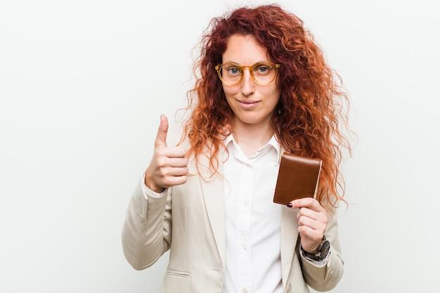 Młoda caucasian rudzielec kobieta trzyma portfel uśmiecha się kciuk up i podnosi