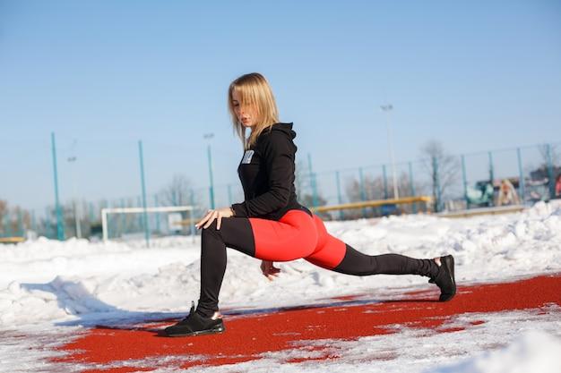 Młoda caucasian żeńska blondynka w fiołkowych legginsach rozciąga ćwiczenie