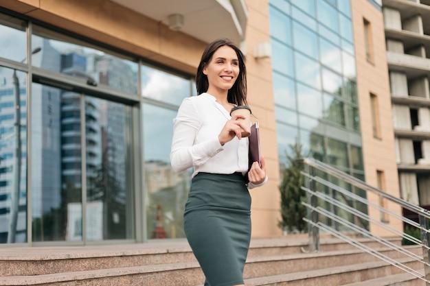 Młoda celowa profesjonalna biznesowa kobieta jest ubranym bluzkę i spódnicę opuszcza centrum biznesu
