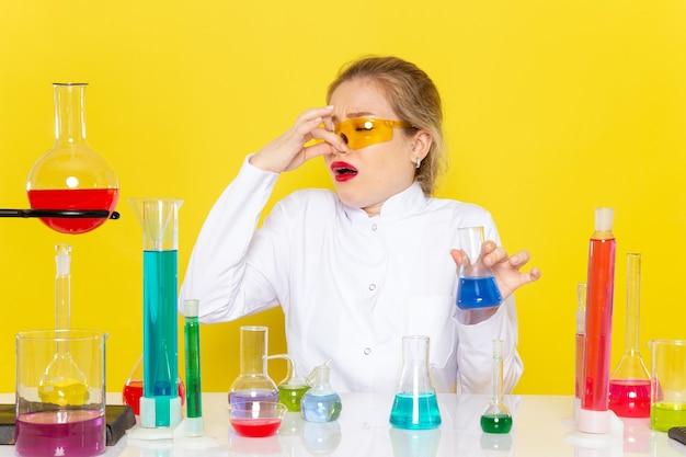 Młoda chemiczka z przodu w białym garniturze z roztworami ed trzyma nos na żółtej kosmicznej chemii