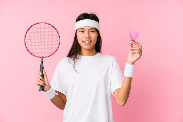 Młoda chinka gra w badmintona na białym tle