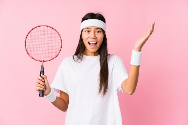 Młoda chinka grająca w badmintona na różowym tle otrzymująca przyjemną niespodziankę, podekscytowana i podnosząca ręce.