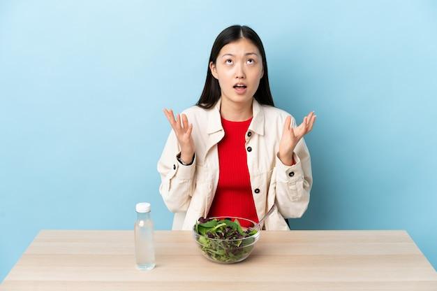 Młoda chinka jedząca sałatkę zestresowana, przytłoczona