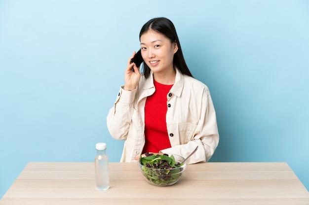 Młoda chinka jedzenie sałatki prowadzenie rozmowy z telefonem komórkowym z kimś