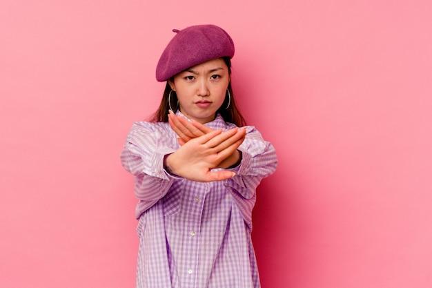 Młoda chinka na białym tle na różowej pozycji z wyciągniętą ręką pokazuje znak stopu, uniemożliwiając ci.