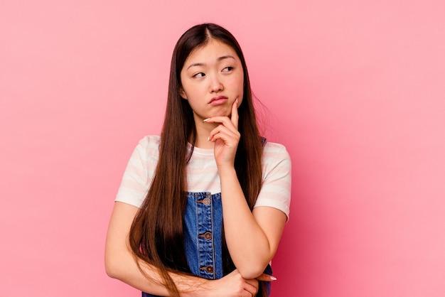 Młoda chinka na białym tle na różowej ścianie kontemplując, planując strategię, myśląc
