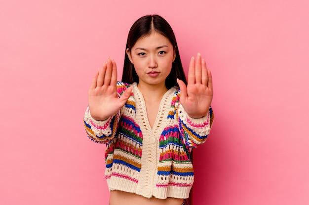 Młoda chinka na białym tle na różowej ścianie stojącej z wyciągniętą ręką pokazując znak stopu, uniemożliwiając ci.
