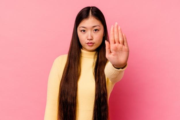 Młoda chinka na białym tle na różowej ścianie stojącej z wyciągniętą ręką pokazując znak stopu, uniemożliwiając ci