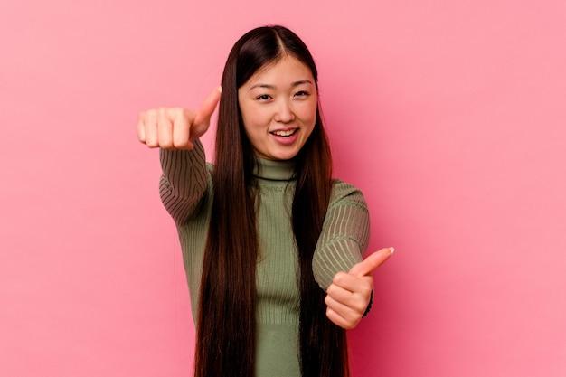 Młoda chinka na białym tle na różowym tle, podnosząc kciuki do góry, uśmiechnięta i pewna siebie.