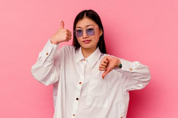 Młoda chinka na białym tle na różowym tle pokazując kciuki w górę i w dół, trudno wybrać koncepcję