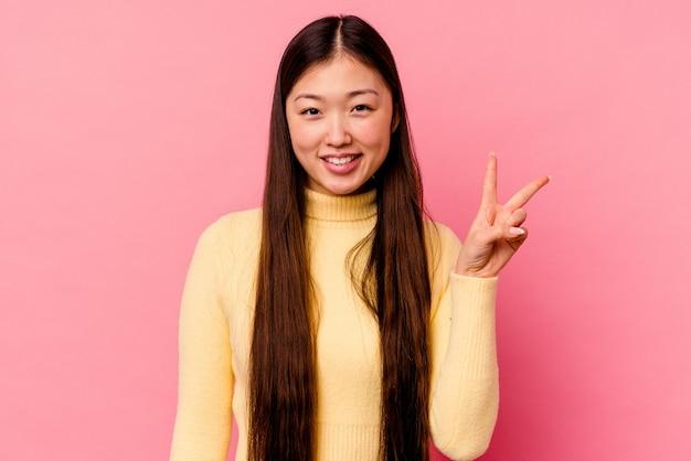Młoda chinka na białym tle na różowym tle pokazując znak zwycięstwa i szeroko uśmiechając się.