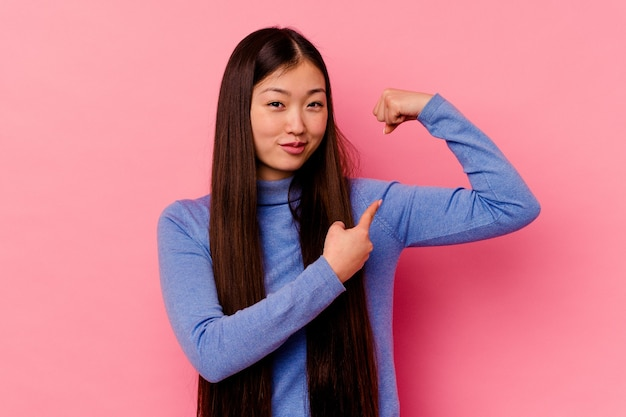 Młoda chinka na białym tle na różowym tle pokazuje gest siły z rękami, symbol kobiecej mocy