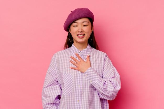 Młoda chinka na białym tle na różowym tle śmieje się głośno, trzymając rękę na piersi.