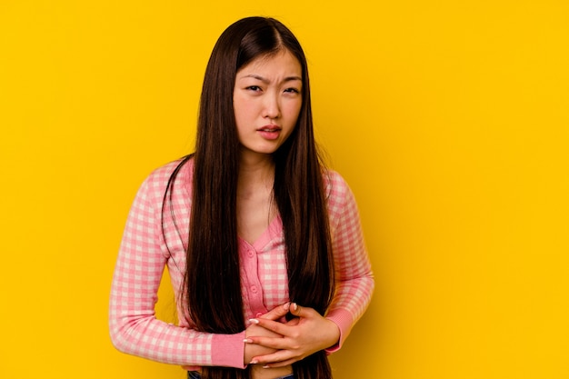 Młoda chinka na białym tle na żółtej ścianie ma ból wątroby, ból brzucha.