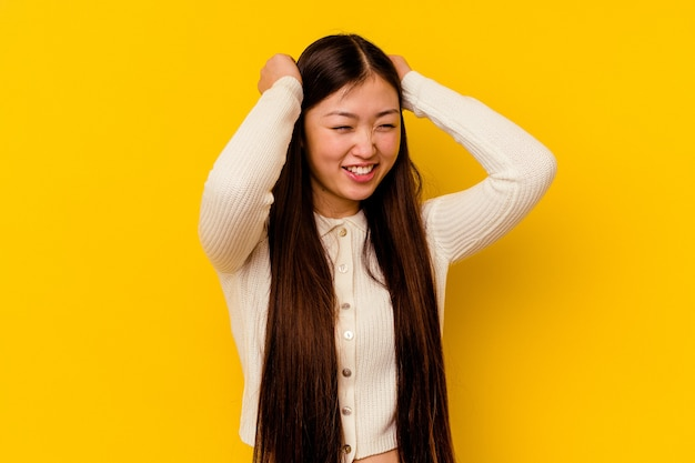 Młoda chinka na białym tle na żółtej ścianie obejmujące uszy rękami.