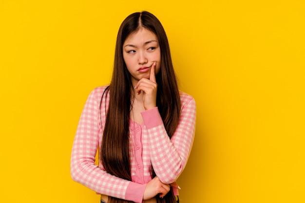 Młoda chinka na białym tle na żółtym tle kontemplując, planując strategię, myśląc o sposobie prowadzenia działalności.