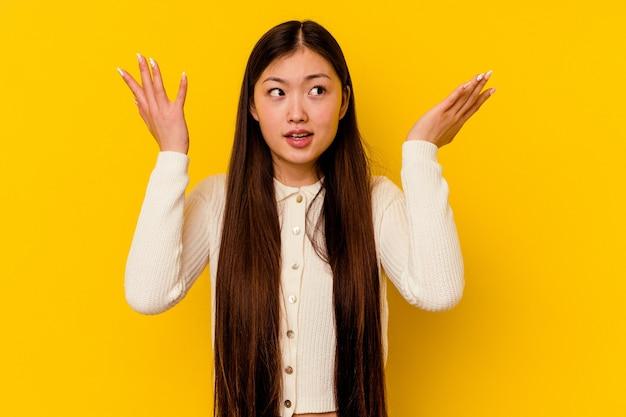 Młoda chinka na białym tle na żółtym tle krzyczy do nieba, patrząc w górę, sfrustrowany.