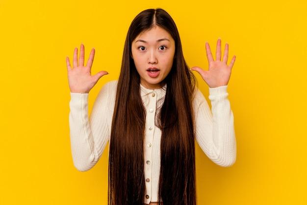 Młoda chinka na białym tle na żółtym tle, mając pomysł, koncepcja inspiracji.