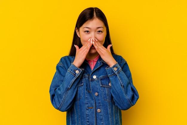 Młoda chinka na białym tle na żółtym tle mówi plotkę, wskazując na stronę zgłaszającą coś.