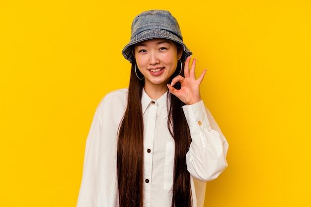 Młoda chinka na białym tle na żółtym tle mruga okiem i trzyma w porządku gest ręką.