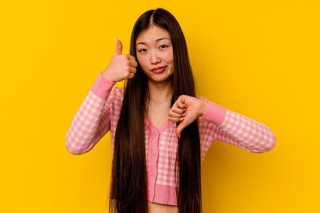 Młoda chinka na białym tle na żółtym tle pokazując kciuki w górę i w dół, trudno wybrać koncepcję