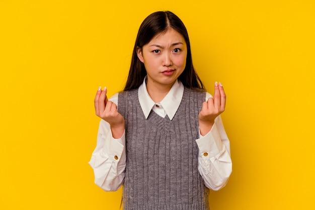 Młoda chinka na białym tle na żółtym tle, pokazując, że nie ma pieniędzy.