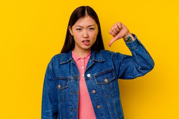 Młoda chinka na białym tle na żółtym tle pokazuje kciuk w dół i wyraża niechęć.