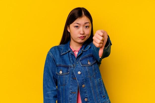 Młoda chinka na białym tle na żółtym tle pokazuje kciuk w dół, pojęcie rozczarowania.