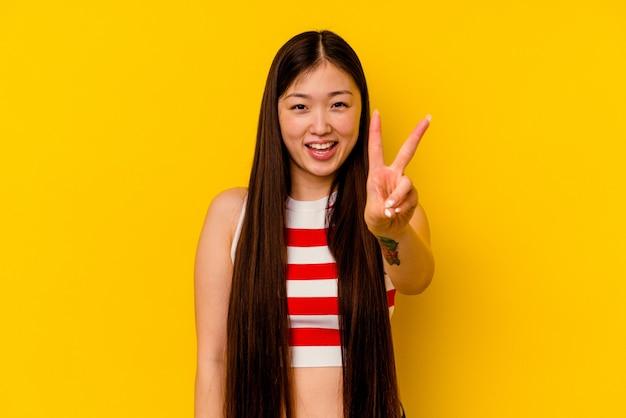 Młoda chinka na białym tle na żółtym tle pokazuje numer dwa palcami.