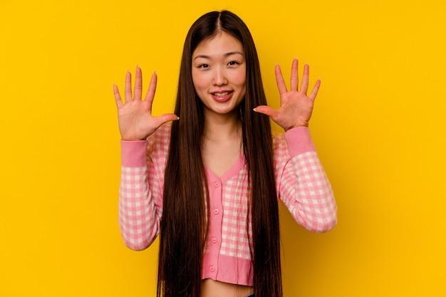 Młoda chinka na białym tle na żółtym tle pokazuje numer dziesięć rękami.