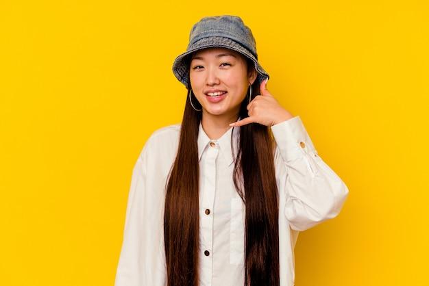 Młoda chinka na białym tle na żółtym tle przedstawiający gest telefonu komórkowego palcami.