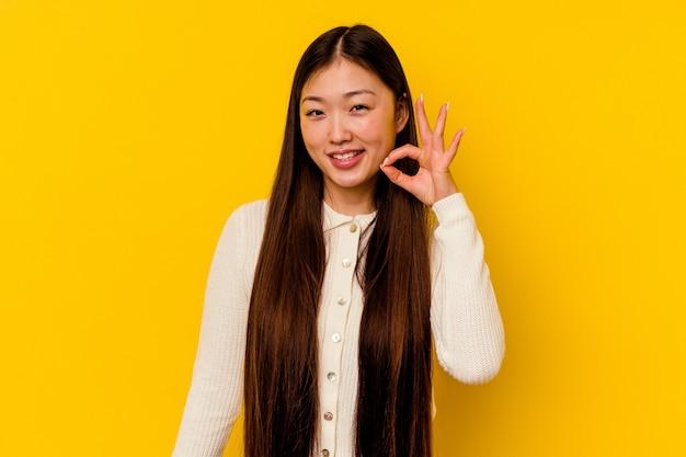 Młoda chinka na białym tle na żółtym tle wesoły i pewny siebie, pokazując gest ok.