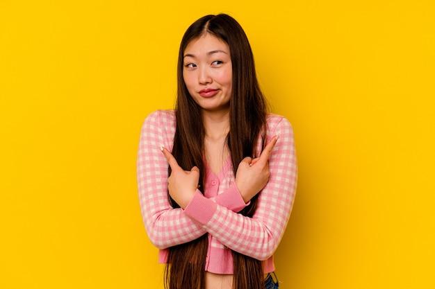 Młoda chinka na białym tle na żółtym tle wskazuje bokiem, próbuje wybrać jedną z dwóch opcji.
